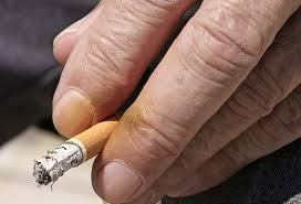 stained yellow fingers holding a burning cigarette