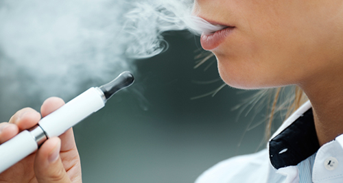 half a women's face shown exhaling vapour with electronic cigarette in her hand