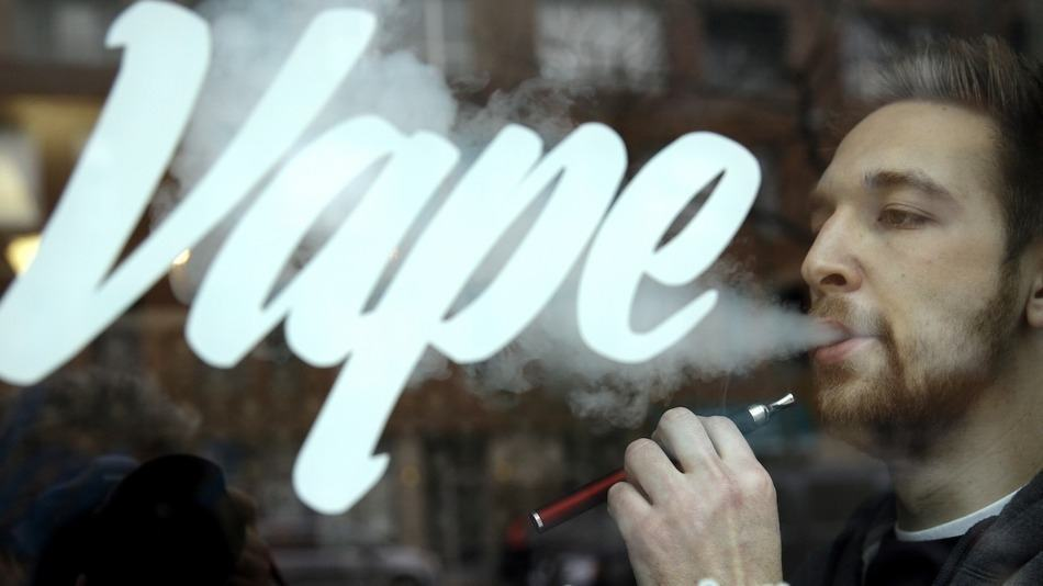 Guy vaping and in the vapour is the word Vape
